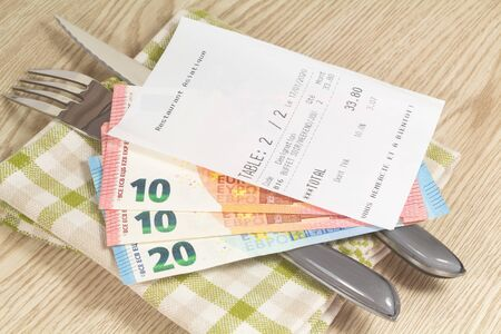 Fork, knife, napkin and restaurant bill with asian restaurant, buffet, thank you and see you soon written in french language Reklamní fotografie