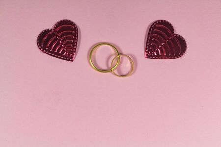 Two wedding rings and two hearts on pink background 版權商用圖片