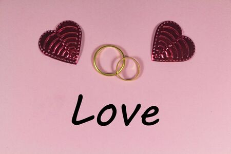 Two wedding rings, love and two hearts on pink background