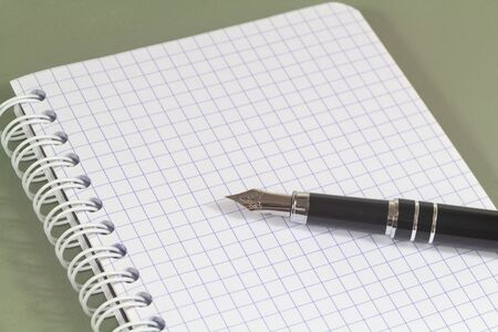 Open lined notebook and black fountain pen