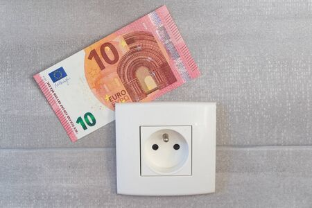 Banknote and socket as concept for the price of electricity 版權商用圖片