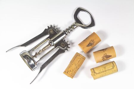 Corkscrew and several corks on white background
