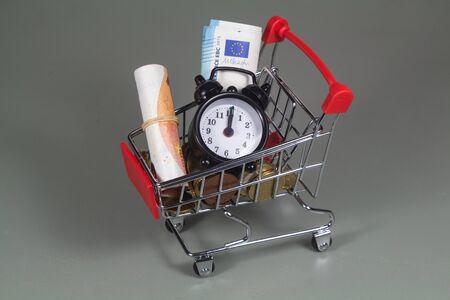 Small shopping cart, black alarm clock, coins and banknotes