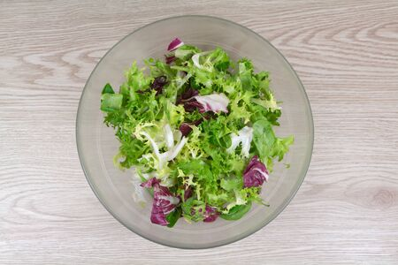 Mixed green salad with lamb's lettuce, curly endive and radicchio in a dish