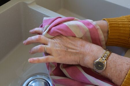 Woman drying her hands with a dish towel