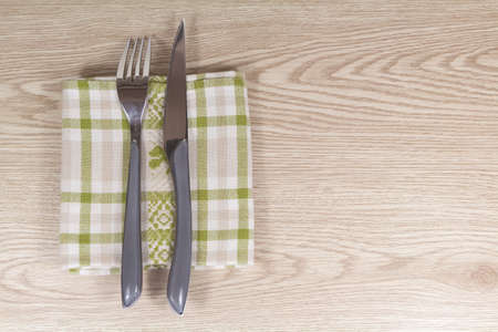 Fork, knife and napkin on a wooden background