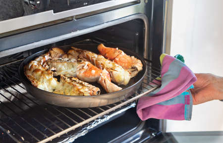 To remove the grilled lobster from the oven with a dish towel