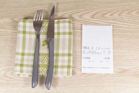 Fork, knife, napkin and restaurant bill on wooden background Standard-Bild