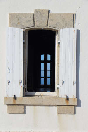 Closed window in an open window with white shutter Standard-Bild