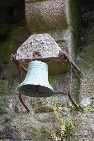 Old bell in copper on a wall made in stone