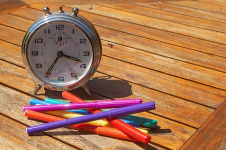 Alarm clock and felt-tip pencils to symbolize time to go back to school 版權商用圖片
