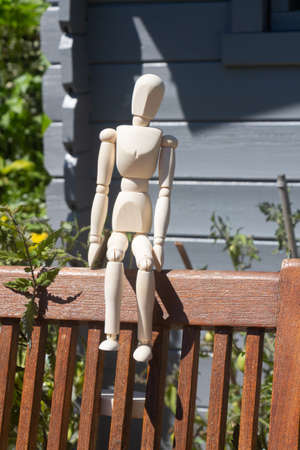 Wooden mannequin for drawing sitting on a chair