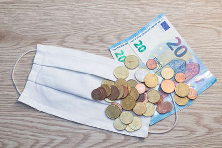 White fabric mask, euros banknotes and coins 版權商用圖片