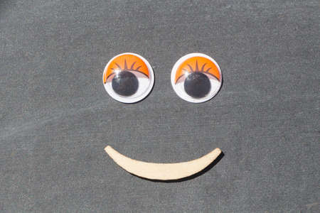 Smiling face made with plastic eyes and wooden mouth