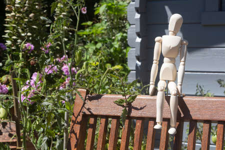 Mannequin for drawing sitting on a chair in a garden