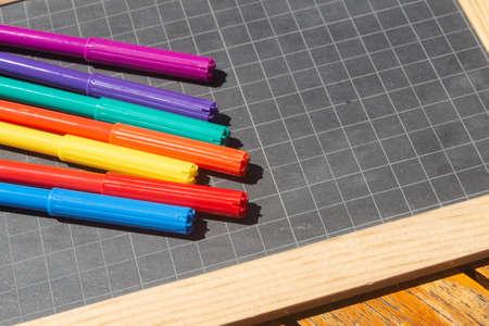 Different colors of felt-tip pencils and chalkboard slate 版權商用圖片