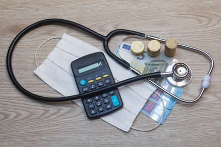 Fabric face mask, black stethoscope, euros banknotes and coins and calculator