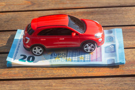 Red toy car on a heap of euros banknotes