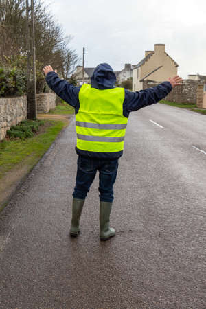 Man with yellow vest stopping cars on the road