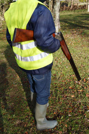 Hunter with its rifle in a forest during autumn