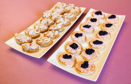 Blinis with taramasalata, lump-fish roe and lobster on white dish
