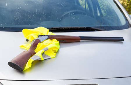 Rifle and yellow vest of a hunter on the bonnet of a car 版權商用圖片