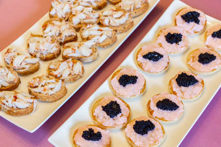 Blinis with taramasalata, lump-fish roe and lobster as appetizer for a cocktail 版權商用圖片