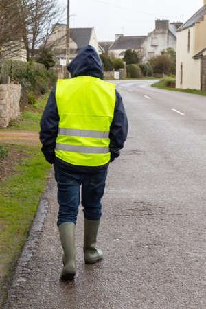 Man with yellow vest walking on the road