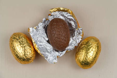Three chocolate eggs wrapped in golden paper for easter