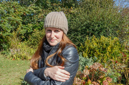 Woman who is cold in a garden during autumn