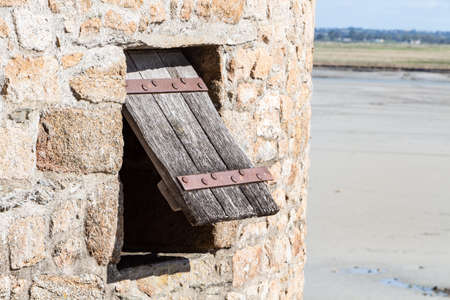 Open wooden shutter in a tower in the ramparts of Mont Saint-Michel Standard-Bild