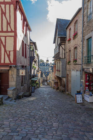 Dinan – France, October 03, 2017 : Old paved street with half-timbered houses and shops in Dinan