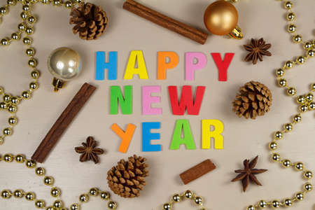 Pine cones, cinnamon sticks, star anise, pearl tinsel and happy new year written in colored letters
