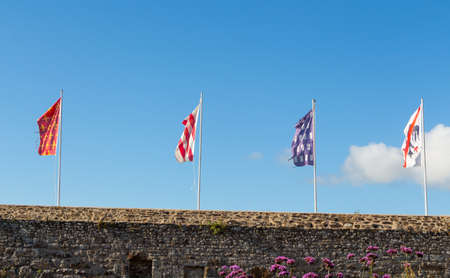 Flags with different emblems on a wall of Dinan castle