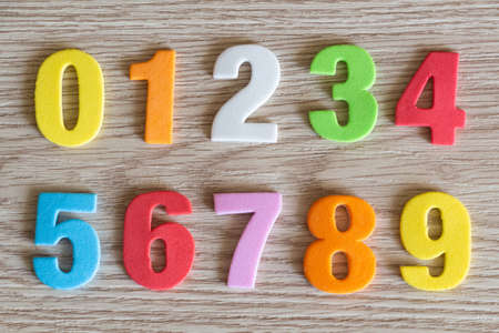 Colored numbers in foam on wooden background
