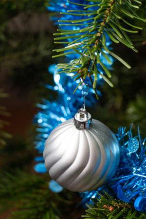 Silvery Christmas balls, blue tinsel on a Christmas tree