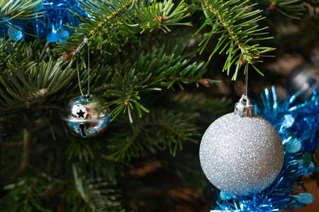 Silvery Christmas balls, blue tinsel on a Christmas tree in a living room Stock fotó