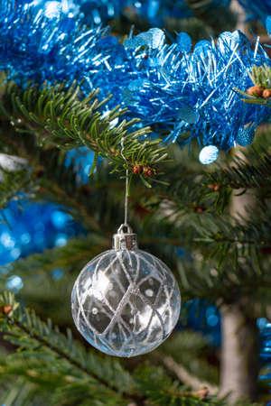 Silvery Christmas ball, blue tinsel on a Christmas tree