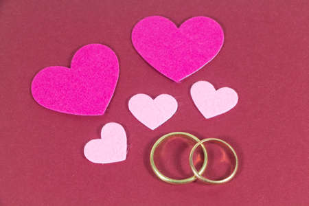 Two wedding rings and pink hearts for Valentine's day