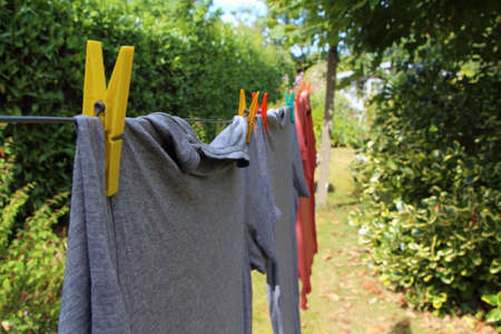 Washing line and pin clothes with grey t-shirts in a garden
