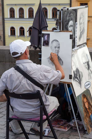 PRAGUE - CZECH REPUBLIC, AUGUST 13, 2019 : portrait painter drawing a face from a picture in a street