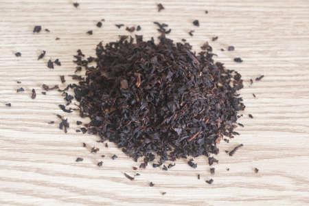 Black tea leaves with jasmine flavor on wooden background
