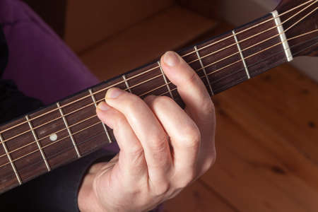 Close-up on the hand of a man playing guitar