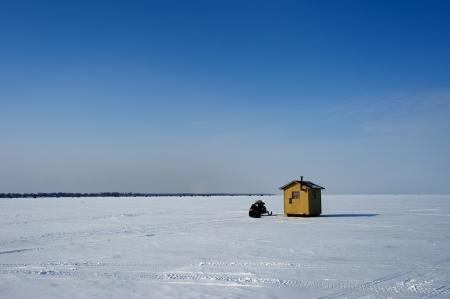 Ice fishing hut on a lake photo