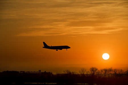 silhouette of a large airplane reach the city at sunset  photo
