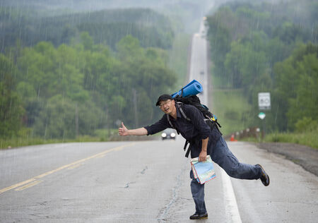 hitch hiker: Hitchhiking travel man at the route  Stock Photo