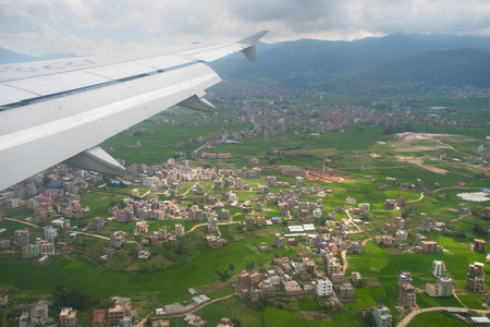 An aircraft is flying over Kathmandu; the Himalayas is the background.