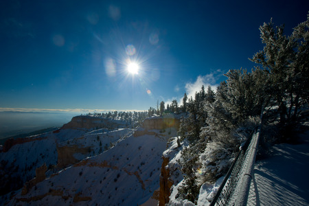 Bryce canyon panorama with snow and fog in Winter with red rocks and blue sky. photo