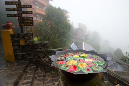 Mano de Nepal martillado vasija de bronce redondo que contiene un poco de agua con pétalos de flores rojas de loto flotando en ella. Foto de archivo - 36764938