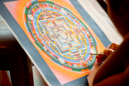 A young artist paints a Tibetan tanka painting in Bhaktapur, Nepal